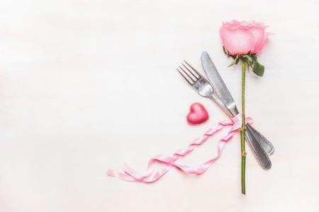 Tafelplek instelling: roos bloem, bestek en lint op lichte achtergrond, bovenaanzicht, plaats voor tekst
