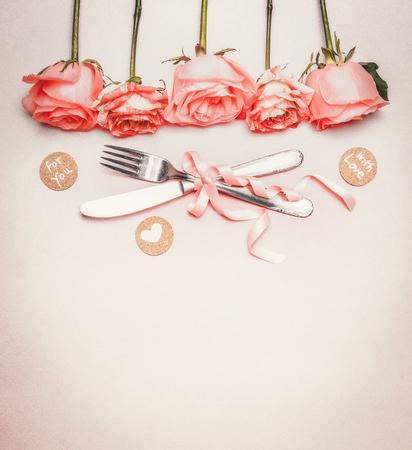 ロマンチックなディナー テーブルの場所の設定と背景: バラ国境、カトラリー、パステル背景、トップ ビューでリボンをテキストの配置
