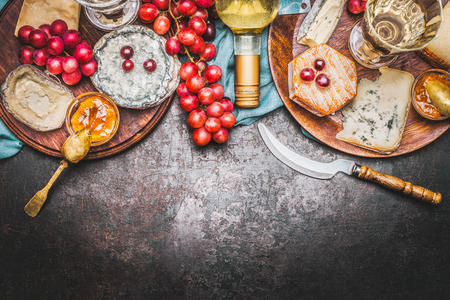 tabla de quesos: Varios selección de queso fino con la botella de vino, salsa de mostaza de miel y uva en el fondo rústico, vista desde arriba, en la frontera Foto de archivo