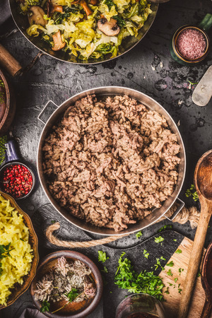 carne picada: Minced Meat in cooking pot on rustic kitchen table with ingredients , rice and cooked cabbage, top view Foto de archivo