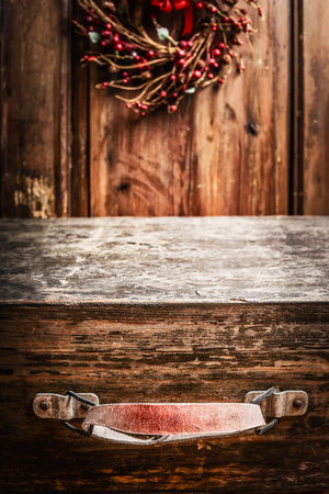 Aged vintage wooden suitcase at rustic background with Christmas wreath Stock Photo