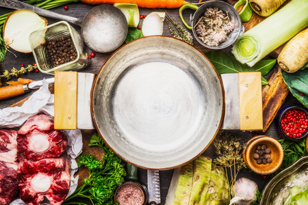 over black: Empty cooking pot with cooking ingredients for meat soup or broth on kitchen table, top view Stock Photo