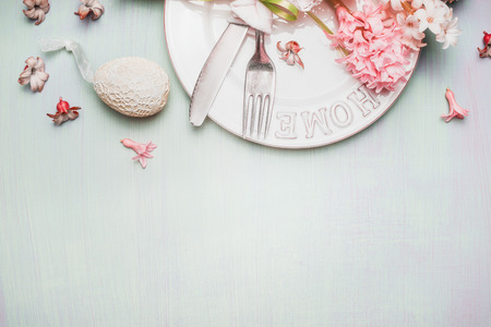 setting: Easter border with table place setting with decor egg and flowers on  light pastel wooden background, top view, place for text