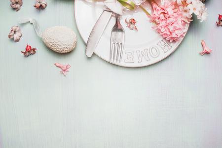 Ostern Grenze mit Tisch Gedeck mit Dekor Ei und Blumen auf hellen Pastell hölzernen Hintergrund, Ansicht von oben, Platz für Text