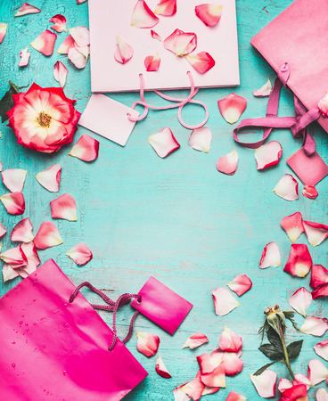 Pink Shopping bags , flowers and blank tags on turquoise background, top view, frame