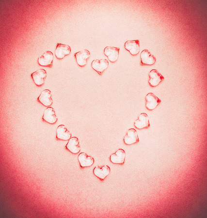 glass texture: Glass hearts composing on pink background, top view