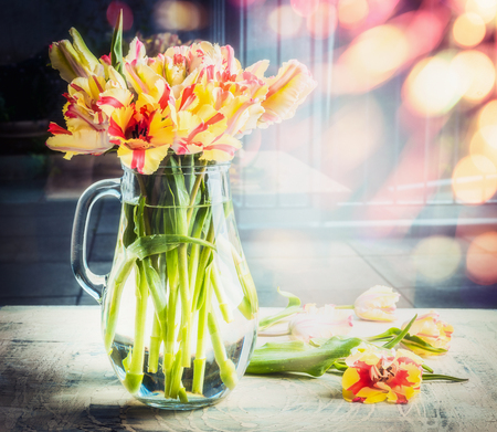 Bright  bouquet of tulips in glass jug on table at sunny spring day background with bokeh, front view