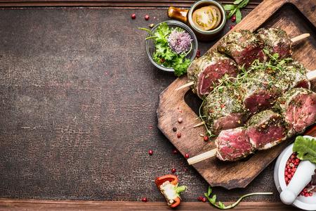 Lekkere Ruwe Vleesspiesjes voorbereiding met verse heerlijke kruiden op rustieke achtergrond, bovenaanzicht, grens