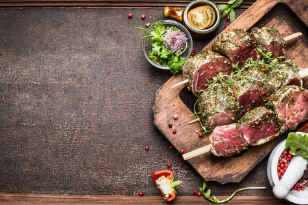 Tasty raw Meat skewers preparation with fresh delicious seasoning on rustic background,  top view, border