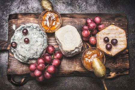 food and drink: Rustic cheese plate with various cheese, grape and honey mustard sauces, top view. Dark style