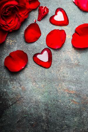 Fondo d'annata di giorno di biglietti di S. Valentino con le rose rosse, i petali ed il cuore, vista superiore, confine, verticale Archivio Fotografico - 69800586