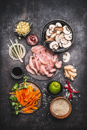 Asian cooking ingredients for chicken rice dish with vegetables on dark rustic background , top view, flat lay