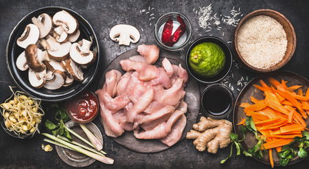 stir: Food ingredients for asian cooking with rice, chicken ,vegetables and spices in bowls, top view Stock Photo