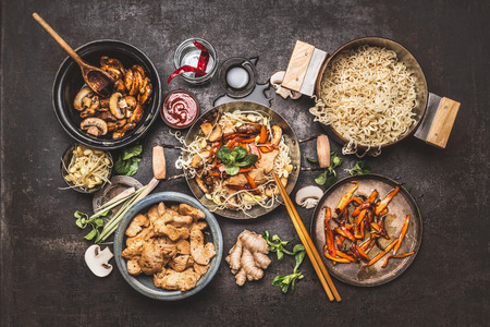 アジアは炒め鶏肉、麺と野菜、暗いヴィンテージ背景に構成する平面図で鍋です。