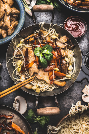 Asian dish with chicken vegetables noodle stir-fry in little wok with chopstick and cooking ingredients, top view