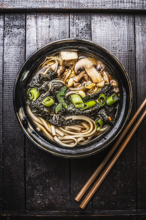 black: Asian ramen soup with noodles, tofu and nori seaweed in bowl with chopsticks on dark wooden background.