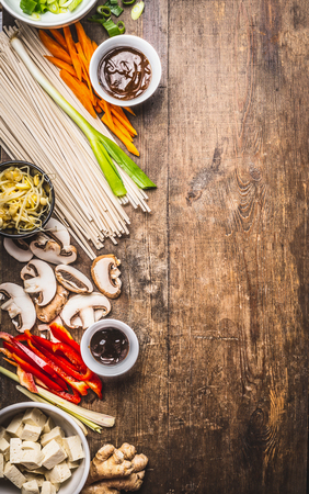 vegetarian cuisine: Various asian cuisine ingredients with  tofu, noodles , spices, vegetables and sauces for tasty vegetarian cooking on rustic wooden background, top view, place for text
