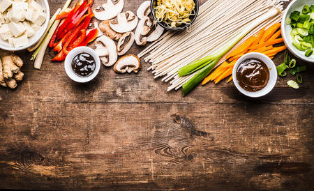 hoisin sauce: Asian vegetarian cooking ingredients for stir fry with tofu, noodles, ginger, cut vegetables, Sprout,green onion , lemongrass, hoisin and austern sauce on wooden rustic background, top view, border