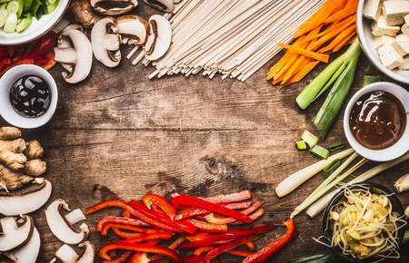 hoisin sauce: Asian food background with vegetarian cooking ingredients and chopsticks : tofu, noodles, ginger, lemongrass, cut vegetables, Sprout,green onion ,hoisin and austern sauce,  top view, frame