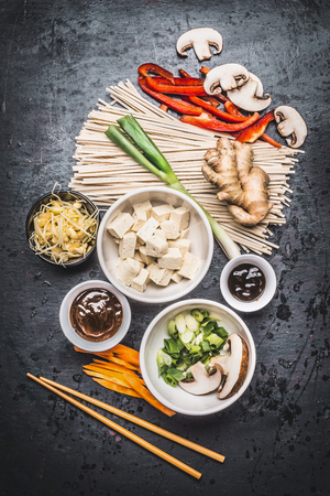 Various Asian vegetarian cooking ingredients and chopsticks with tofu, noodles, ginger, cut vegetables, Sprout,green onion ,hoisin and austern sauce on dark rustic background, top view