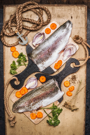 cocina saludable: Raw trout fillet on cutting board with gut vegetables, top view.  Healthy food and diet cooking concept