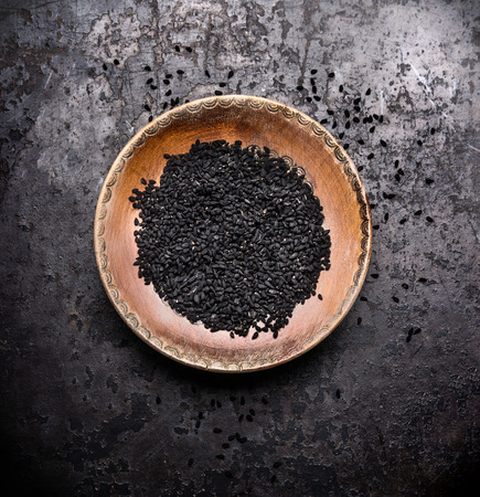 Black cumin seeds in rustic bowl on dark vintage background, top view. Nigella sativa seeds