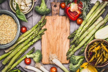Vegetarian ingredients for pearl barley porridge or salad around wooden cutting board, top view.  Healthy clean food or diet nutrition concept Stock Photo