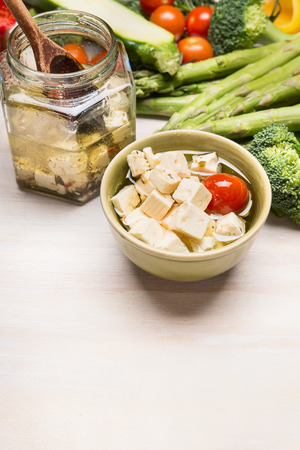 marinated gherkins: Pickled Diced feta cheese in olives oil and vegetables on white wooden background, border, close up