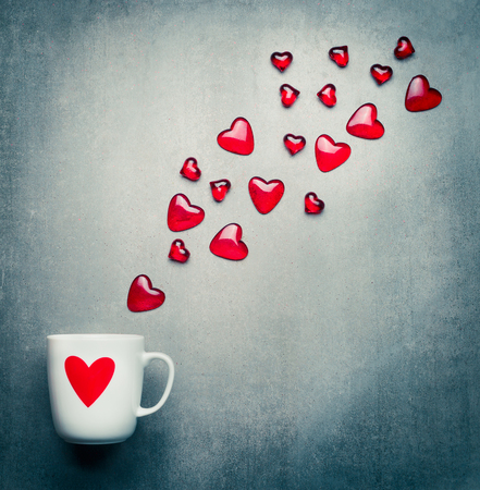Cup with red heart and flying glass hearts . Romantic Love symbols , Valentines day or Birthday concept,  copy space
