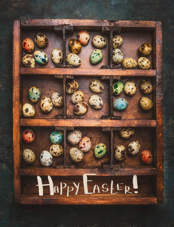 huevos de codorniz: Colored eggs for Easter feast in aged Wooden box on dark rustic background with lettering Happy Easter, top view