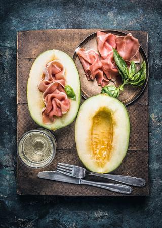 jambon prosciutto savoureux jamon serrano et le melon avec le verre de vin blanc et couverts, vue de dessus