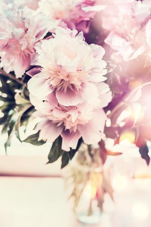Grupo de peonías preciosas en florero de vidrio sobre mesa con iluminación bokeh. Ramo romántico de flores, vista frontal, color pastel