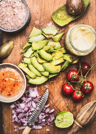 cocina saludable: Cut avocado with knife and Healthy cooking ingredients for tasty salad or dip , top view Foto de archivo