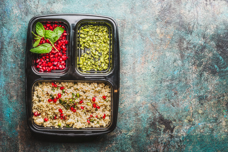 Healthy lunch box with salad, pomegranate and pistachios nuts on rustic background, top view, place for text