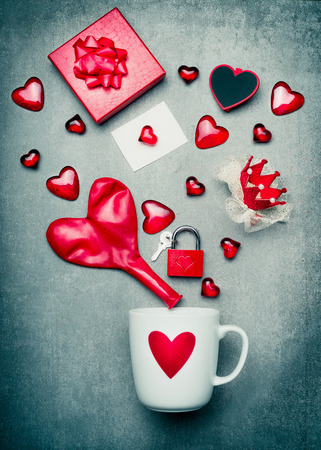 lock symbol: Cup with heart symbol and red Valentines day decoration with gift box, greeting card, lock and key, crown and balloon in heart form.