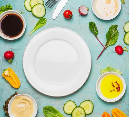 vegetarian food: Healthy food background with salad ingredients with various dressing and blank plate, top view. Diet eating, Vegetarian or vegan food concept