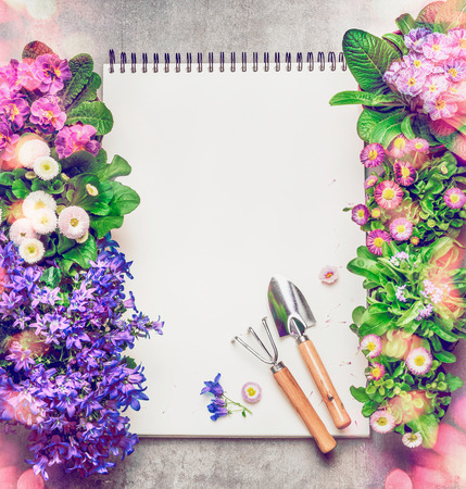 garden frame: Floral Gardening background with assortment of colorful garden flowers in pots , blank paper notebook and gardening tools, top view, frame