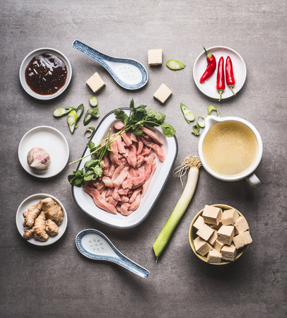 spicy cooking: Various asian cooking ingredients in bowls for spicy asian soup with tofu and meat :  sliced meat, ginger, chili, diced tofu ,Oyster sauce, garlic and broth, top view, flat lay Stock Photo