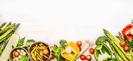 white: Variety of organic vegetables ingredients with asparagus and feta for delicious seasonal cooking , white wooden background, top view, place for text, banner