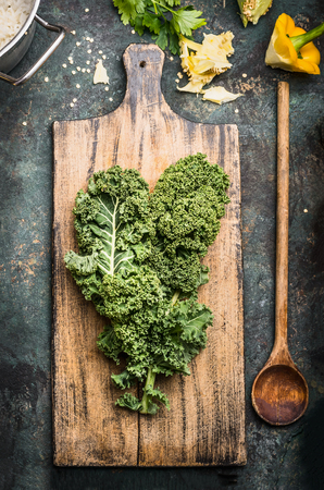 wooden board: Green kale leaves on rustic cutting board with wooden cooking spoon , top view