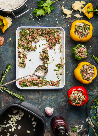 Bell colorful paprika peppers stuffing preparation with rice and mincemeat on rustic kitchen table background, top view