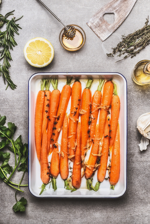 cocina saludable: Roasted Carrots with thyme, garlic, lemon and honey on baking try , cooking preparation. Healthy root vegetables concept Foto de archivo