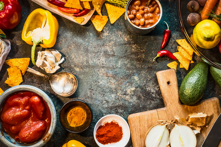 vegetarian cuisine: Vegetarian cooking ingredients for Mexican cuisine: canned Beans, Peeled tomatoes, paprika,chili, onion,lemon, spices , avocado and tacos or tortilla chips on dark rustic background, top view, frame Stock Photo