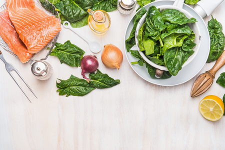 Spinach leaves and salmon fillets with ingredients on white kitchen table background, cooking preparation, top view, border. Diet nutrition and healthy food concept