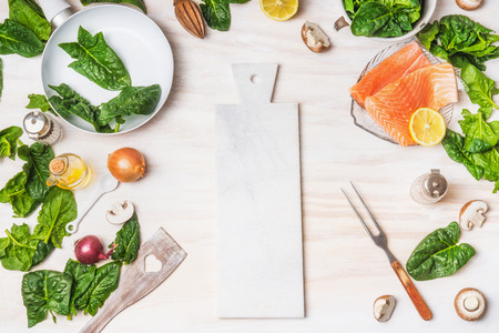 Healthy or diet  food background with cutting board, organic spinach leaves, salmon, pan ,fork and cooking ingredients on white kitchen table background, top view, place for text