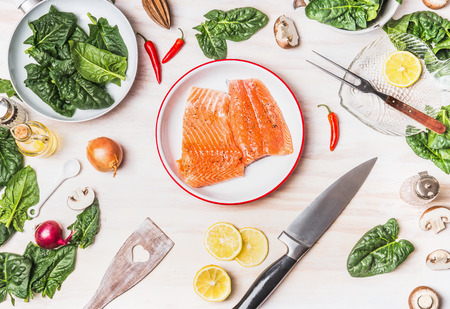 Top view of kitchen table with salmon , spinach leaves , kitchen knife and pan, cooking preparation on white wooden background , top view Фото со стока - 71828106