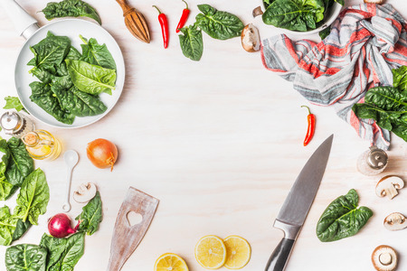 blanch: Healthy vegetarian cooking with spinach leaves on white wooden background with kitchen knife and ingredients, top view frame. Vegan or diet food concept