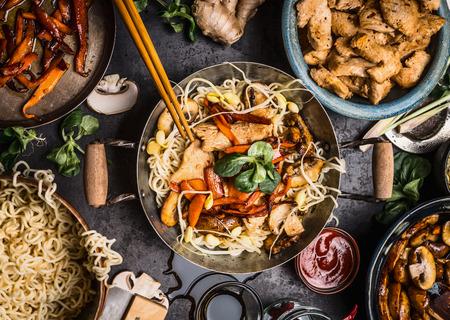 フードボウル、鍋、炒め物、箸、背景、平面図上の成分を持つアジアン キッチン テーブル