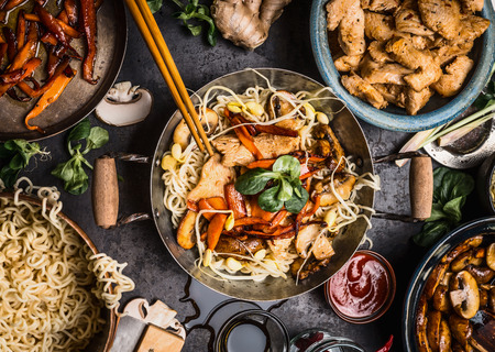 Asian kitchen table with food bowls, wok , stir fry , chopsticks and ingredients on background, top view Banco de Imagens