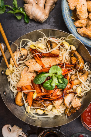 Wok with noodles chicken stir fry and chopsticks, top view, close up. Asian cuisine concept
